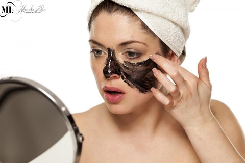 Woman applying a black facemask while looking in the mirror - ML Delicate Beauty