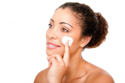 Picture of a woman with colored eyes applying moisturizer on her face   ML Delicate Beauty