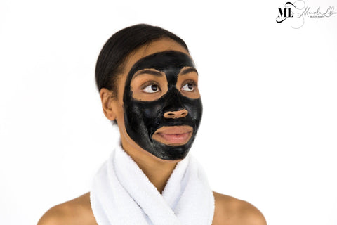 Woman with a charcoal face mask - Skincare treatment