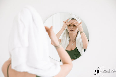 woman massaging her forehead in the mirror - ML Delicate Beauty