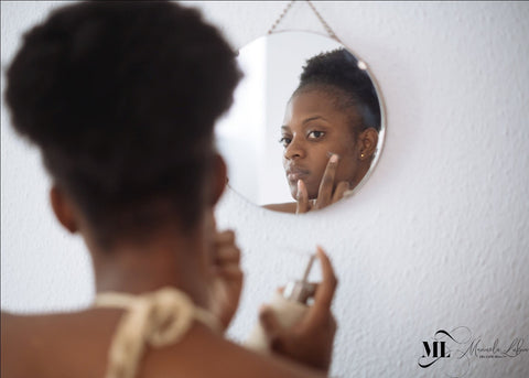 Woman applying cream looking in the mirror