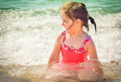 Little girl giggles while sitting in ocean waves