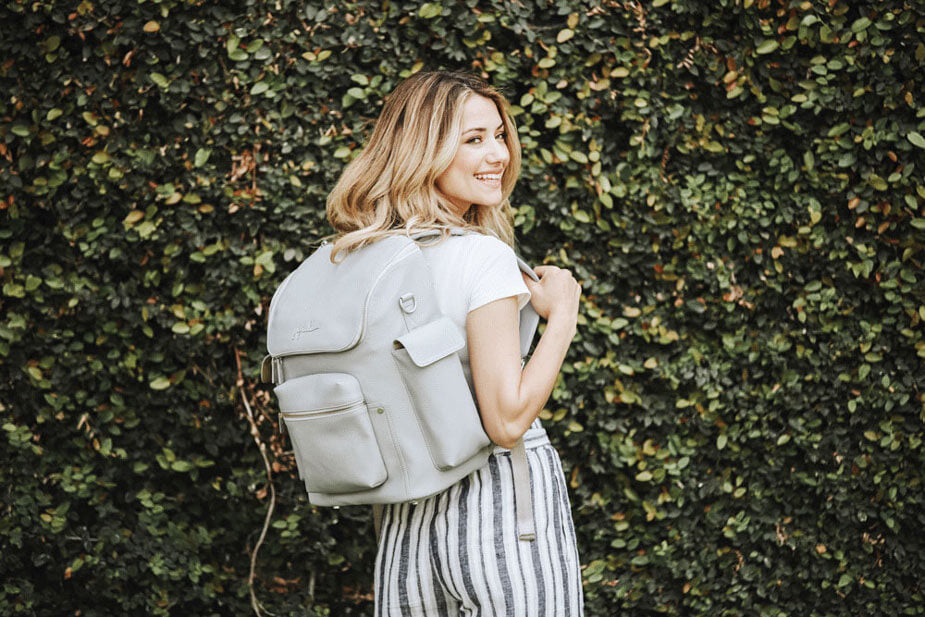 Woman poses with her white, JuJuBe backpack