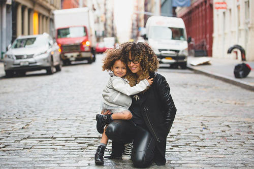 Mom holds her small daughter on cobblestone street