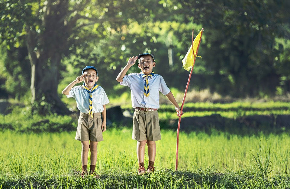 Two boys in Boy Scout outfits solute the camera