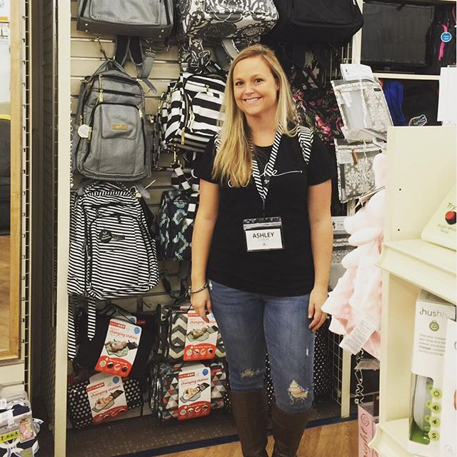 Woman poses next to wall full of JuJuBe diaper bags