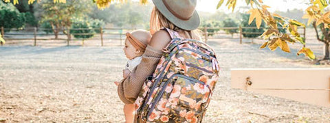 Woman holds her baby while walking through park