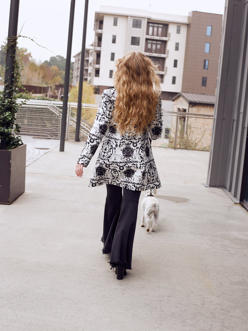 Trendy woman models a horse riding coat with an equestrian pattern and velvet details.