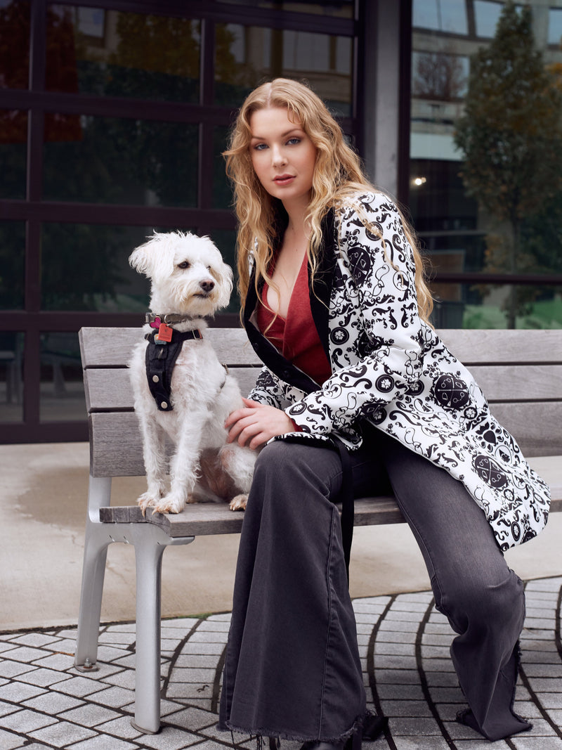 Woman models an equestrian themed jacket while sitting on a bench in the city with a poodle rescue dog.
