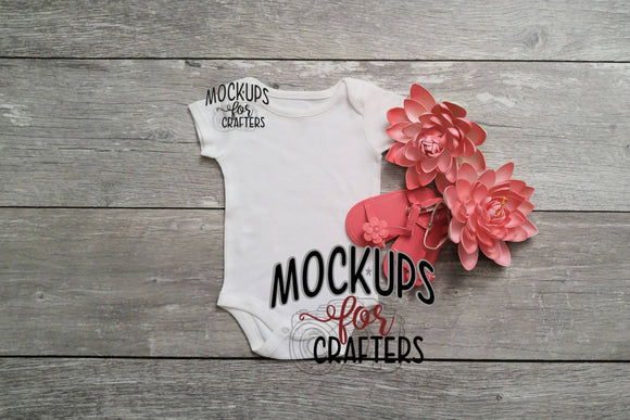 Baby bodysuit mock-up includes coral sandals and flowers