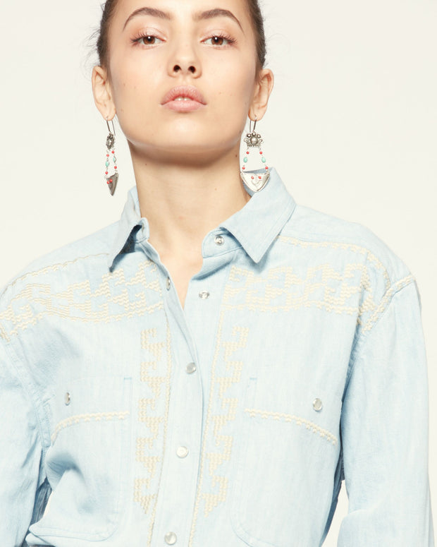 Close up of model from the waist up wearing a light denim button down with embroidering at the chest and large statement earrings.