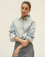 Model with a serious expression and arms crossed wearing a light denim button down and dark denim skirt.