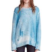 Woman in an oversized distressed blue sweater facing the camera with arms down by her sides.