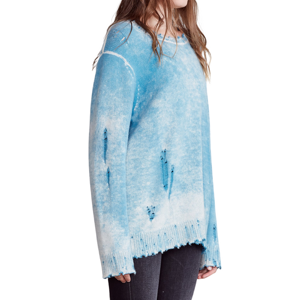 Woman in light blue distressed sweater facing to the side.