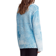 Woman in oversized baby blue distressed cashmere crewneck sweater facing away from the camera.