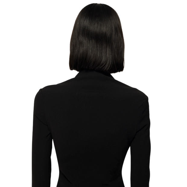 Back of woman's upper body with dark slightly wavy bob haircut and long sleeve plain black top. Woman is facing away from the camera.