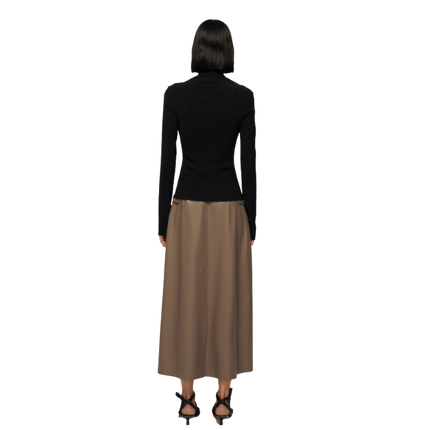 Full length shot of a woman facing away from the camera  with a short dark bob style haircut. She is wearing a long sleeve black top with an angular square neckline, long sleeves an army green midi skirt  and black kitten heel sandals.