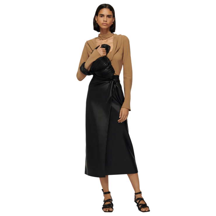 Woman standing with weight on back foot with a short blunt bob, tan long sleeve shirt, black leather wrap skirt that hits at mid calf and sandals.