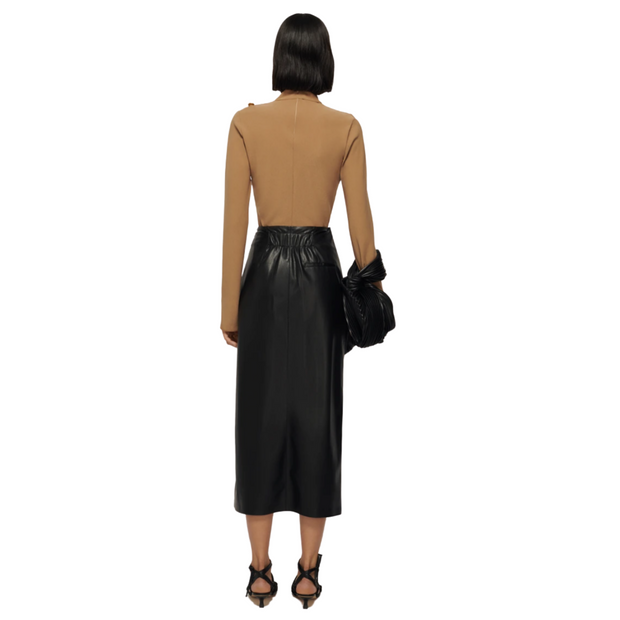 Woman with her back to the camera standing straight wearing a tan long sleeve top, and black leather midi skirt.