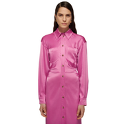 Top three quarters of a woman with sleep hair wearing a long sleeved lustrous pink button down shirt dress