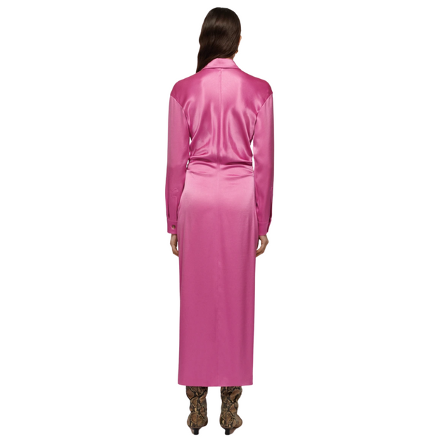 Woman standing straight facing away from the camera wearing long sleeved pink satin shirt dress.