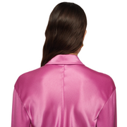 Chest and up shot of a woman wearing a long sleeve pink satin shirt with collar.
