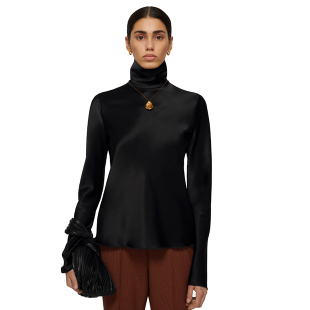 Top half of woman standing and looking straight ahead wearing a black turtleneck and gold pendant necklace.