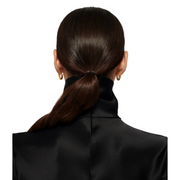 Close up of back of woman's head with sleek ponytail, gold hoop earrings, and satin black turtleneck.