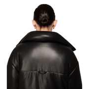 Woman facing away from the camera with her hair pulled back into a slick bun and wearing a lustrous black faux leather jacket.