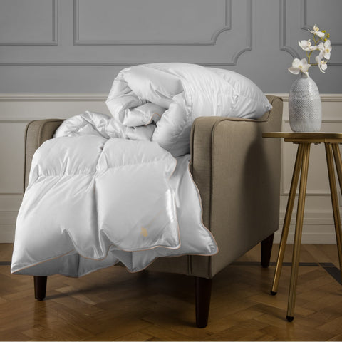 beautiful white down comforter folded on armchair