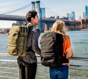 Two travelers in New York City wear the unisex Pakt Travel Backpack. The bag is available in both black and green.