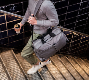 Grey Pakt One duffel bag carried by a shoulder strap on one shoulder by a male model while walking up the New York City subway steps.