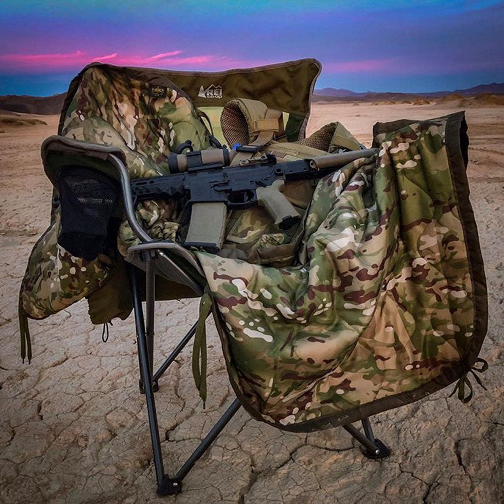 Woobie Blanket Poncho Liner on travel chair with a gun resting on it