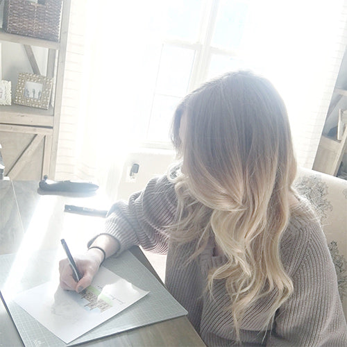 Jessica McGinley, artist and CEO of JesMarried illustrating in her home office