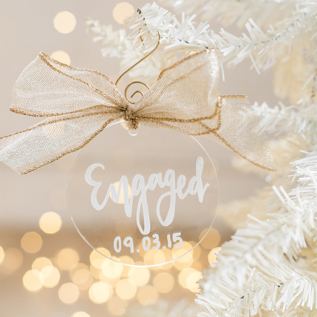 custom hand lettered engaged with date acrylic ornament perfect to gift to bride and groom for christmas or at an engagement party.