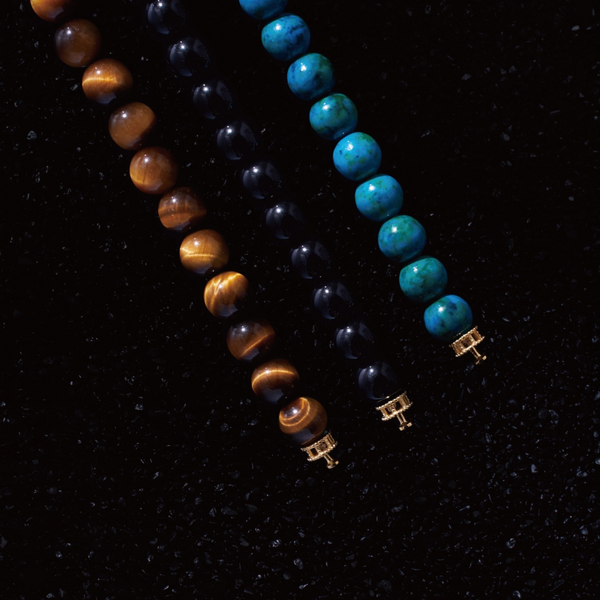 Selected three men's beaded bracelets, obsidian, turquoise, and tiger eye match perfectly with Azuro Republic gold charm beads. The beaded bracelets cover the main color choices for men, black, blue, brown, and portrait a subtle gentleman look.