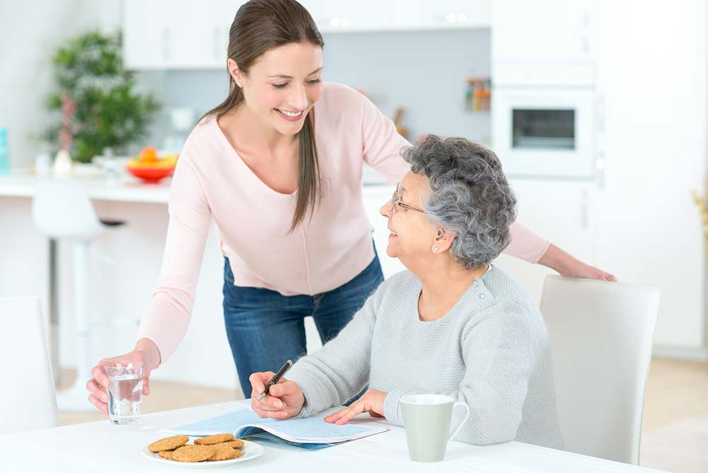 Woman in aged care facility with carer