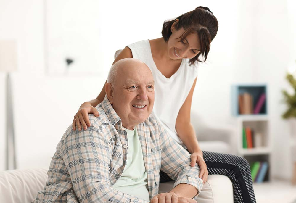 Elderly man and carer sitting on an aged care chair