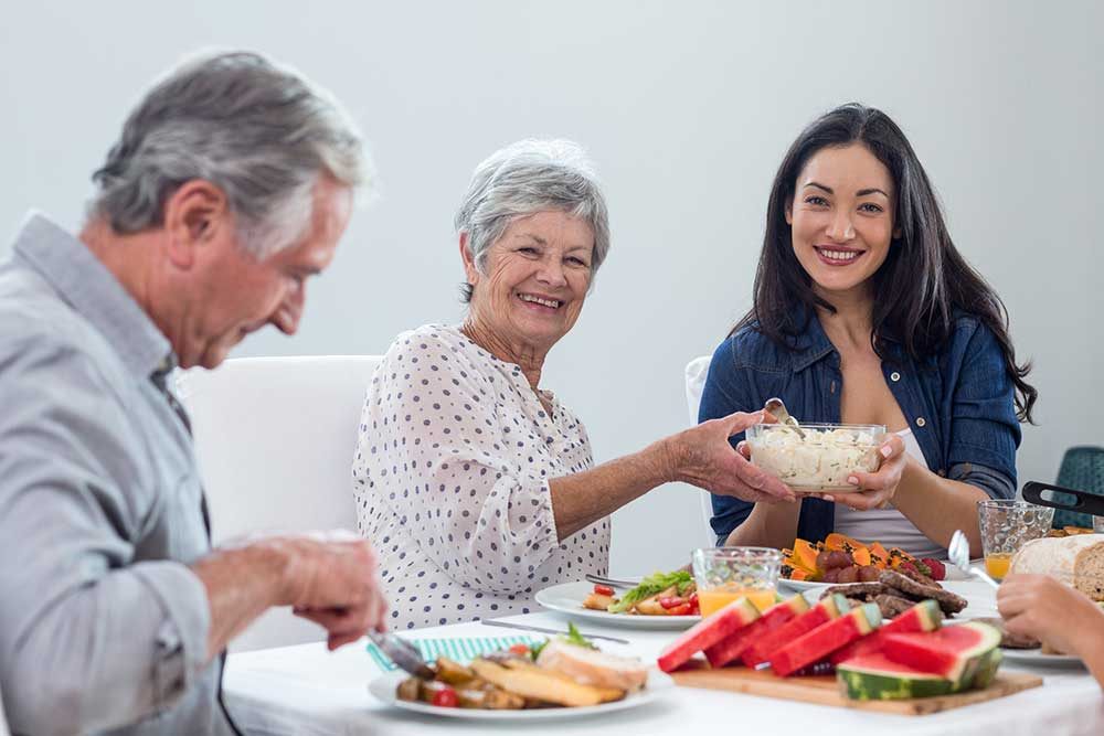 elderly couple with family enjoying meal time