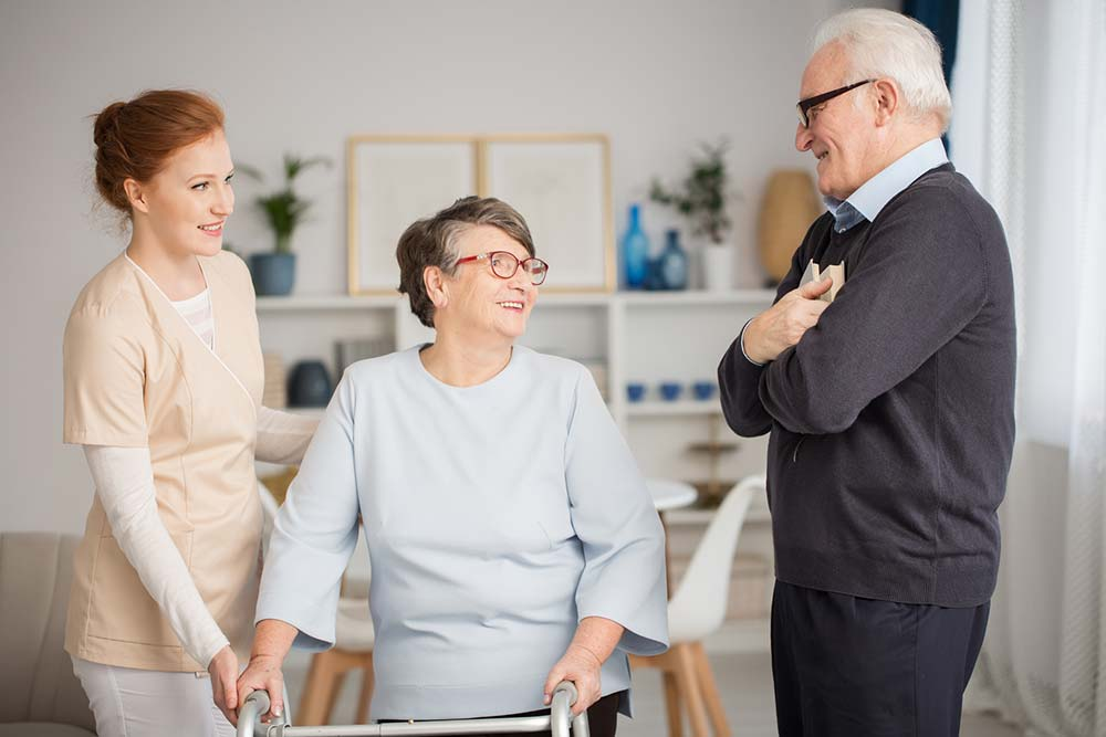 Carer and elderly couple in Brisbane aged care facility