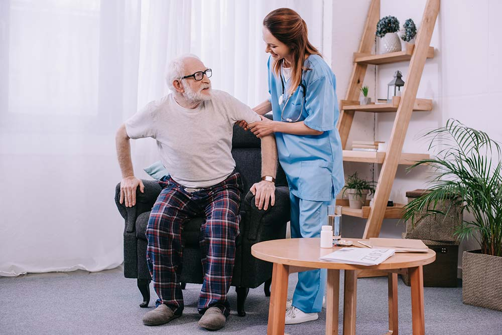 Elderly man trying to stand from an aged care chair