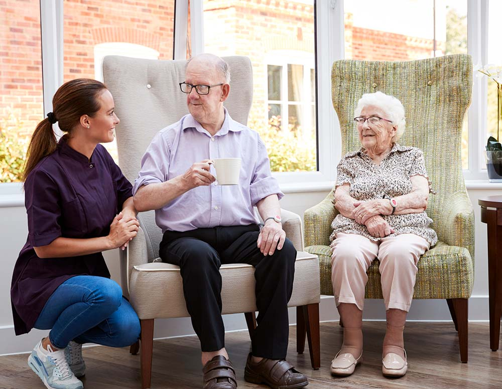 Elderly couple in aged care home sitting on chairs