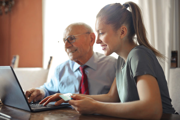 A woman in a grey T-shirt and an old man in a white shirt sitting in front of a laptop