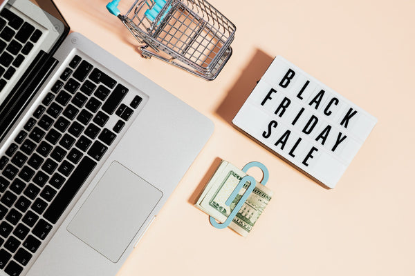A keyboard, shopping cart, dollars, and a placard with Black Friday Sale written on it