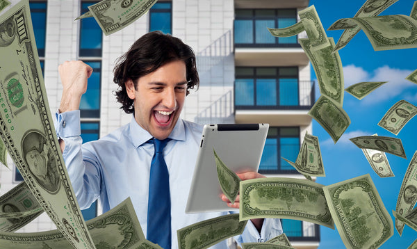 A man in a white shirt and blue tie smiling looking at his tablet with dollars all around him.