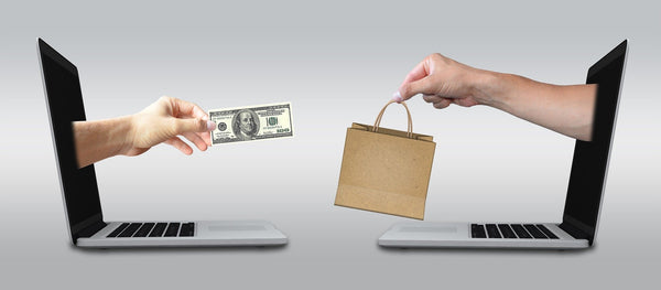 An illustration of eCommerce selling with two hands coming out of different desktop screens holding money and product