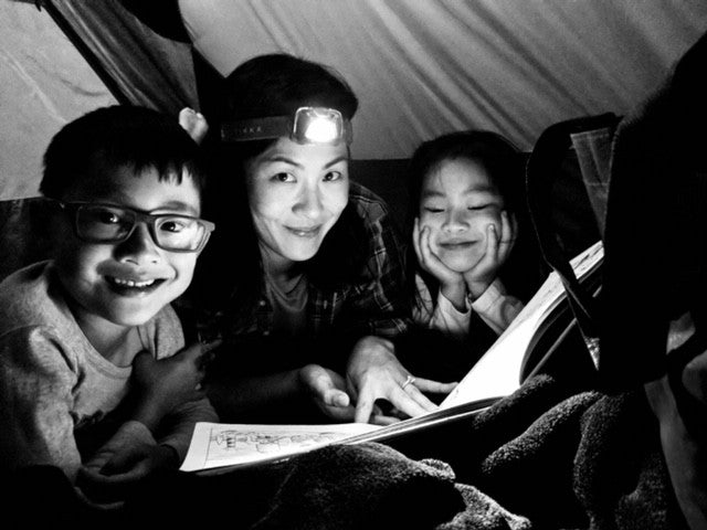Tien reading to her kids on a recent camping trip.