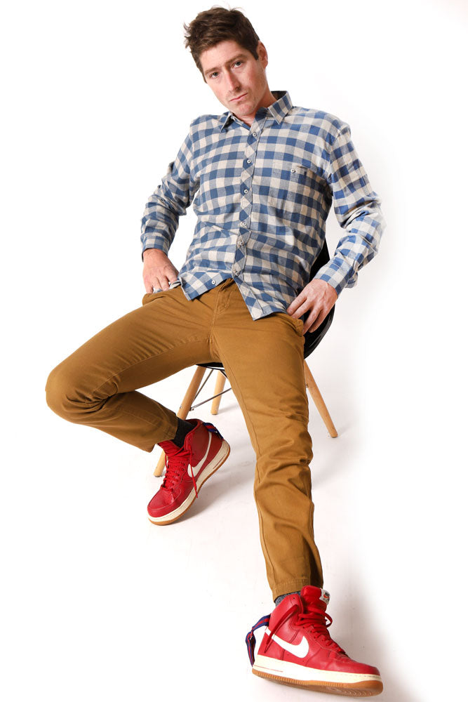 man lounged in chair, wearing bright red shoes, blue and cream plaid shirt, and toast colored pants.