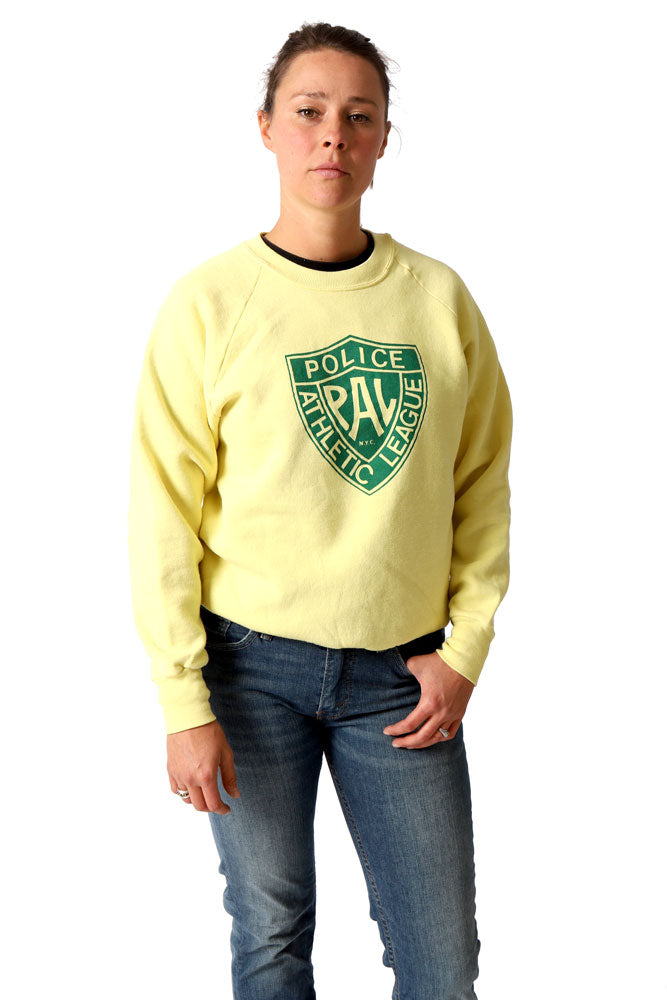 women in vintage police athletic league sweatshirt, in yellow, looks at camera with one thumb in jean pocket.
