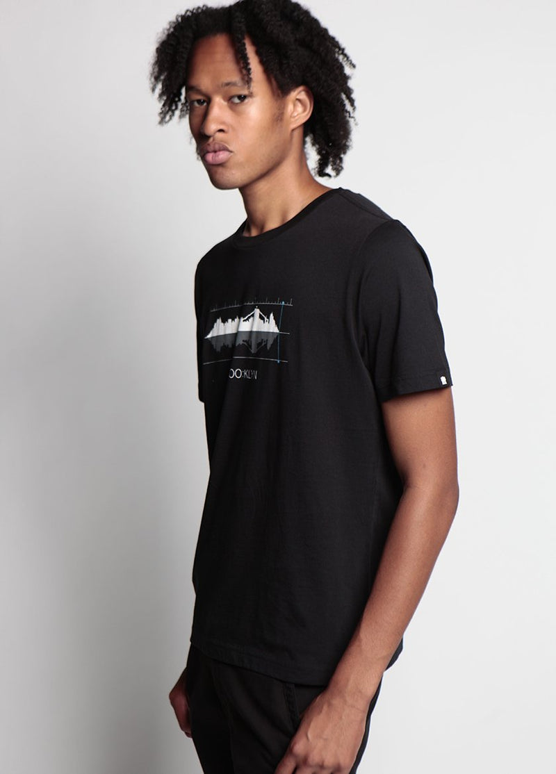 SIDE VIEW OF MAN IN SOUNDWAVE / SKY LINE GRAPHIC T- WITH HANDS AT HIS SIDE